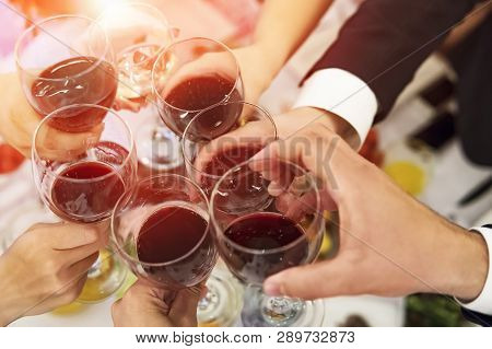 Male And Female Hands With Filled Glasses Of Wine Above The Restaurant Tabletop. Drinking Toasts And