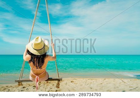 Asian Woman Wear Swimwear And Hat Swing The Swings At Sand Beach  And Looking Beautiful Tropical Par