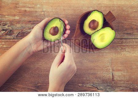 Female Hands Holding Spoon And Half Of Fresh Ripe Avocado. Woman Peeling Avocado. Green Avocado On W