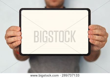 Close Up Of A Digital Tablet In Mans Hands. An Upper Half Shot Of A Man Holding A Tablet With White