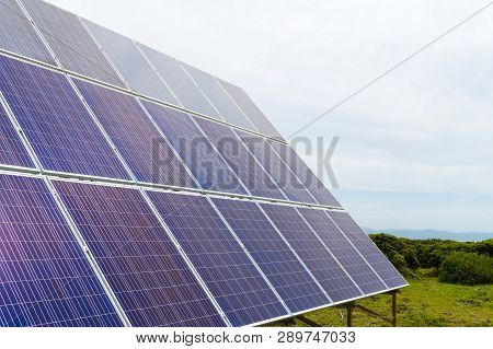 Solar Cell Photovoltaic Panels At Energy Production Plant With Blue Cloudy Sky In The Background