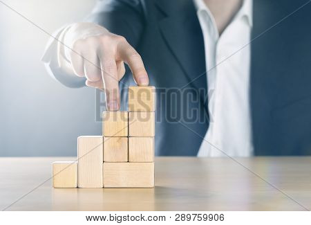 Business Man Walking Up Next Step With Fingers On Career Ladder Made From Wooden Blocks; Career Or A