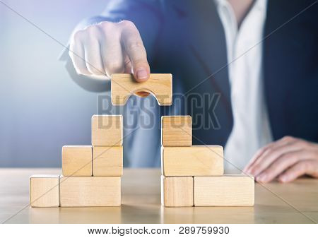 Business Man Bridging The Gap Between Two Towers Or Parties Made From Wooden Blocks; Conflict Manage
