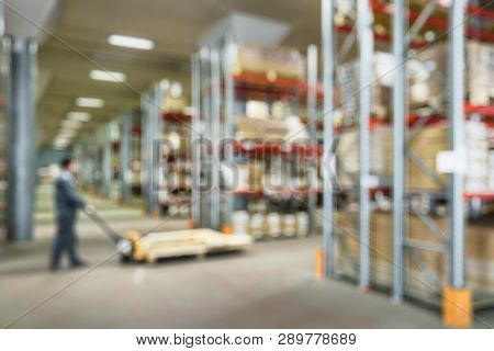 Panorama Of Warehouse Interior As Abstract Blur Background. Worker With Fork Pallet Truck Stacker Wo