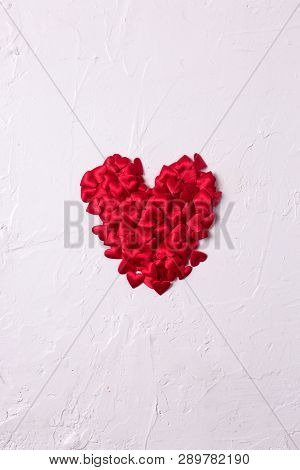 Heart Made From Little Red Textilled Hearts  On  White Textured  Background.  Flat Lay. Place For Te