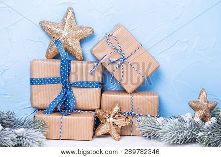 Stack Of Wrapped Boxes With Presents, Fir Tree Branches  And Golden Stars On  Blue Textured Backgrou