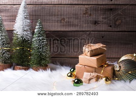 Pile Of Wrapped Presents, Decorative Fir Trees, Golden And Green Balls And Fairy Lights On White Fur