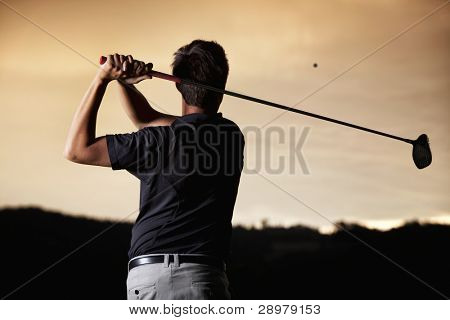 Close up of male golf player in black shirt teeing-off ball in twilight, view from behind.
