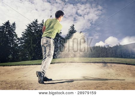 Male golf player in green shirt and grey pants hitting golf ball out of a sand trap with sand wedge and sand caught in motion.