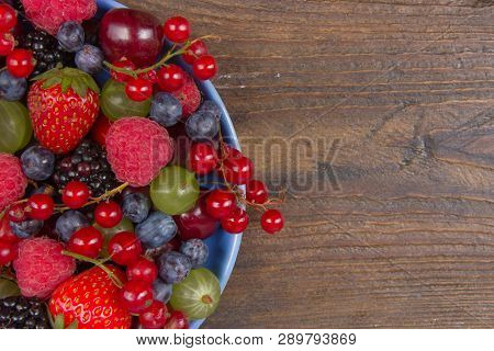 Various Summer Fresh Berries In A Bowl On Rustic Wooden Table. Antioxidants, Detox Diet, Organic Fru