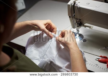 Female Clothier Stitching With Her Hands On Workplace In Atelier. Draping Process With Steel Needle.