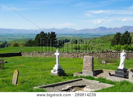 View across old cemetery with broken headstones to expansive rural fields and distant hills in Central Otago New Zealand poster