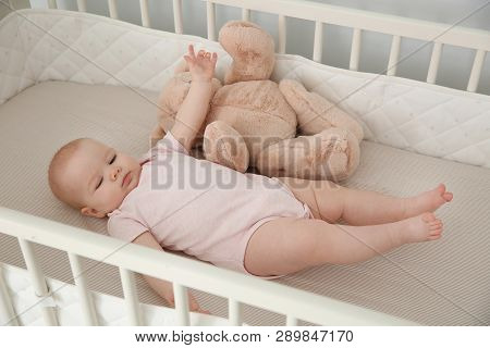 Cute baby girl with toy in crib at home. Bedtime schedule poster