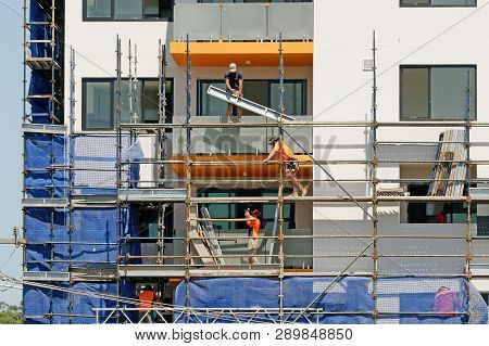 Gosford, New South Wales, Australia - March 4, 2019: Workers Disassembling Scaffolding And Removing