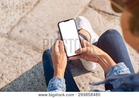 Closeup of young woman hand holding mobile phone with blank screen. Top view of girl using smartphone sitting on the stairs outside. High angle view of african woman unlocking cellphone.
