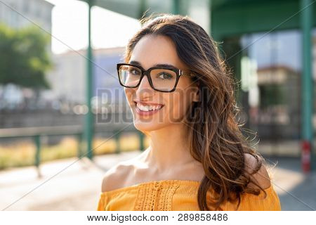 poster of Portrait of carefree young woman smiling and looking at camera with urban background. Cheerful latin girl wearing eyeglasses in the city. Happy brunette woman with long hair and spectacles smiling.