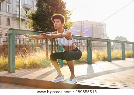 Sporty woman doing squats exercises in the city. Brazilian girl doing sit ups on stairs. Concentrated woman doing warmup squat in urban background.