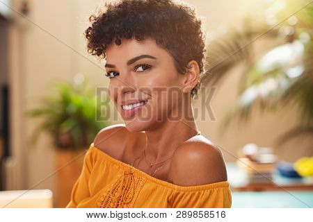 Portrait of natural beautiful girl smiling and looking at camera. Closeup face of brazilian young woman with curly hair. Charming african woman sitting at cafeteria.