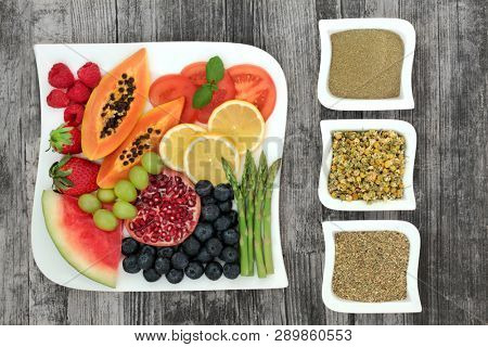 Super food and herbs for weight loss concept with fresh fruit and vegetables with herbs used in herbal medicine to help lose weight and suppress appetite. Top view on rustic wood.