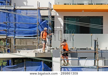 Gosford, New South Wales, Australia - March 6, 2019: Workmen Close Up, Dismantling Scaffolding And R