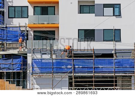 Gosford, New South Wales, Australia - March 6, 2019: Workmen Dismantling Scaffolding And Removing Sa