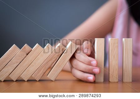 Girl's Hand Stopping Falling Wooden Dominoes Effect From Continuous Toppled Or Risk.