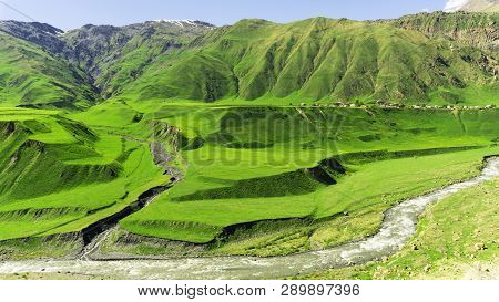 The Village Is On A Mountain Plateau. Mountain Slopes Are Covered With Bright Green Vegetation. Moun