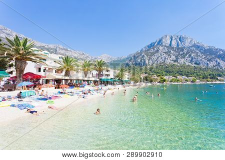 Gradac, Dalmatia, Croatia, Europe - August 24, 2017 - Several Tourists Bathing And Relaxing At The B