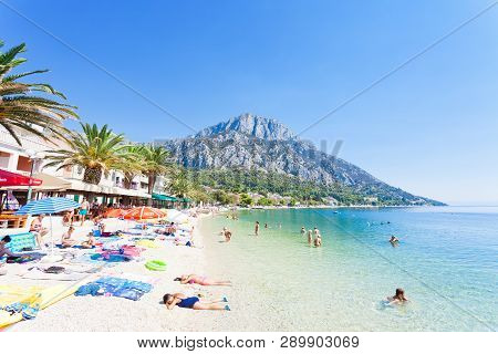 Gradac, Dalmatia, Croatia, Europe - August 24, 2017 - People Bathing And Relaxing At The Promenade O