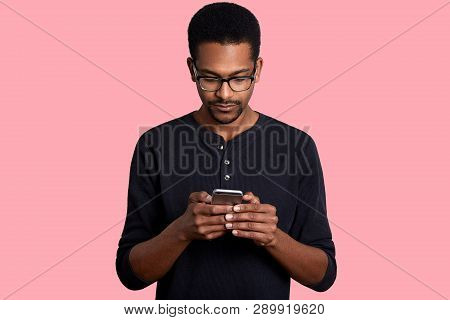 Confident Young African Man Looks At Smart Phone And Sends Text Messege, Connected To Wireless Inter