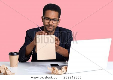 Thoughtful Black Businessman Tries To Write Poem In Notebook For Her Girlfriend While Working On Lap