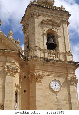 Historic Church Bell Chimes Out The Half Hour At The Parish Church In Xaghra, Gozo, Malta