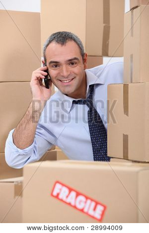 a 40-45 years old employee calling someone in a room full of cardboard boxes