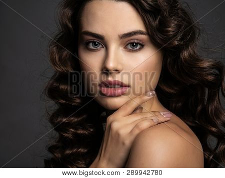 Closeup face of a beautiful woman with a smoky eye makeup. Sexy and gorgeous brown-haired woman with long curly hair. Portrait of an attractive female posing at studio.