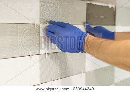 Installing Ceramic Tiles On The Wall In Kitchen. Placing Tile Spacers With Hands, Renovation, Repair