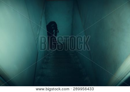 Dark Figure On The Old Concrete Stairs In The Descent To The Basement. Horror Movie Concept.