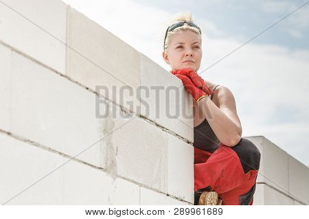 Woman Wearing Dungarees Thinking About Future Of Building Her Home. Female Sitting On Wall Made Of A