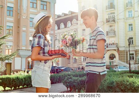 Teen Boy Congratulates Girl With Bouquet Of Flowers And Gift, Outdoor Portrait Couple Happy Youth.