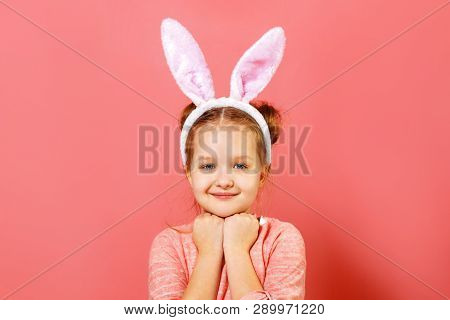 Portrait Of A Cute Little Child Girl With Bunny Ears On A Colar Pink Background. Easter Concept. Clo