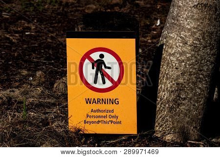 Warning Authorized Personnel Sign On The Ground Next To Tree