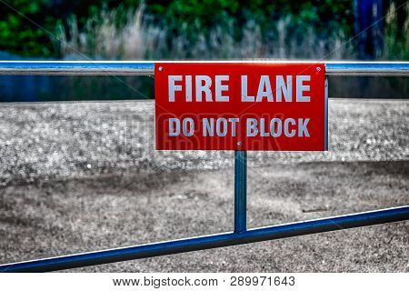 Fire Lane Do Not Block Sign On A Fence In Daylight
