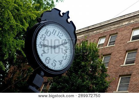 Outdoor Clock In Front Of A Brick Wall And Trees