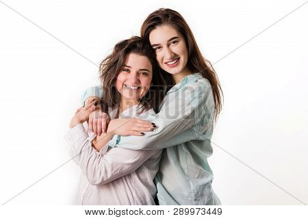 Two Young Girls Hug On A White Background.