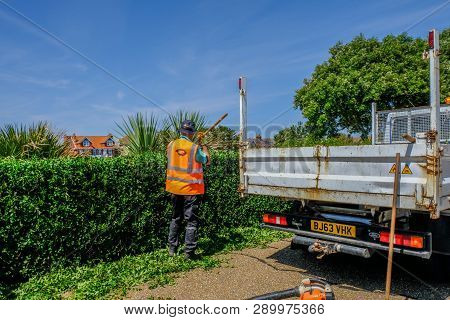 Eastbourne, Sussex, England, Uk - August 1, 2018: Workmanj Raking The Trimmings Of A Newly Cut Edge.