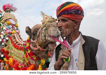 Bikaner, India - January 13, 2019: Indian Man In National Clothes Kisses A Camel During Camel Festiv