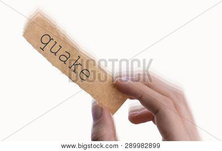 Hand Holding A Piece Of  Torn Notepaper With Quake Wording