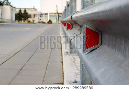 Red Road Reflectors Along The Road. Zinked Or Galvanized Metal Road Fencing Of Barrier Type, Close-u
