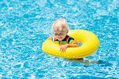Baby with inflatable armbands in swimming pool. Little boy learning to swim in outdoor pool of tropical resort. Swimming with kids. Healthy sport activity for children. Summer vacation. Swim aids. poster