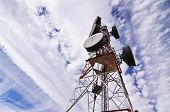 Telecomunication antenna under clouded sky. poster