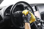 A man cleaning car with yellow microfiber cloth. Car detailing or valeting concept. Selective focus. Car detailing. Cleaning with sponge. Worker cleaning. Car wash concept solution to clean poster